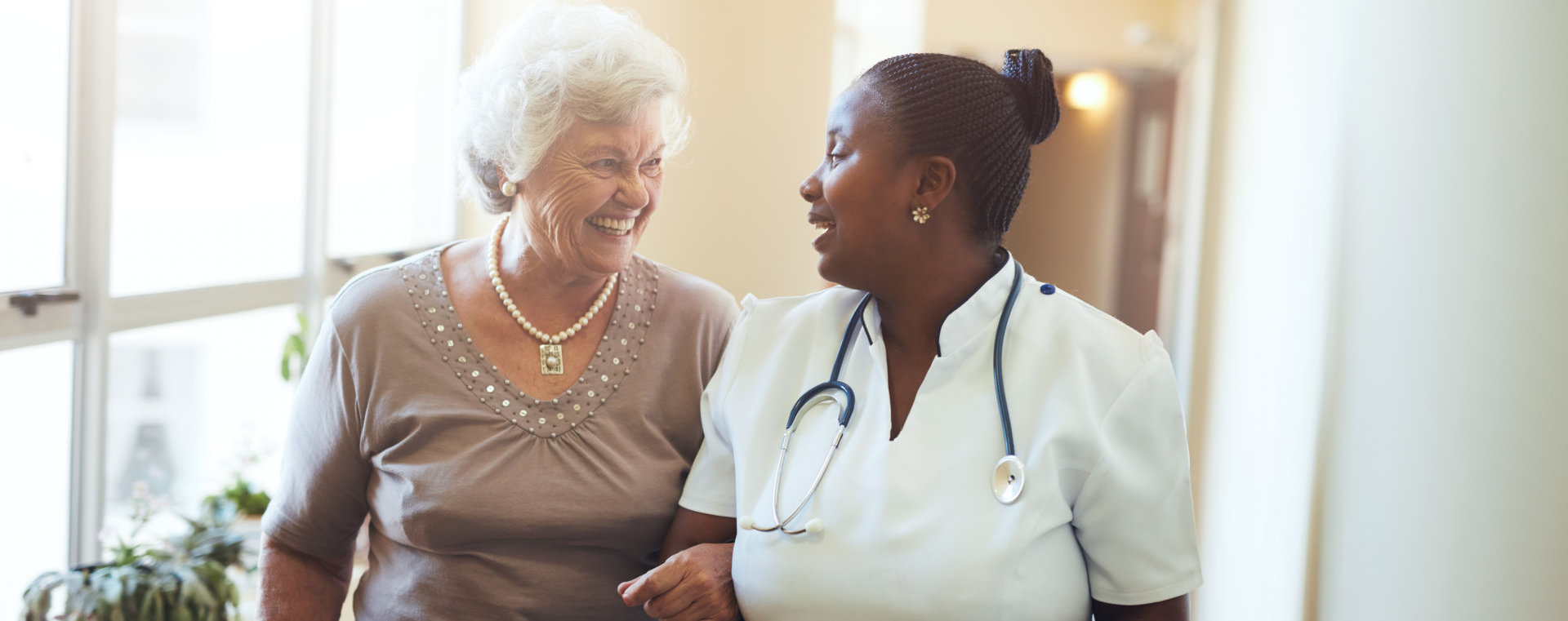 african caregiver and a senior woman