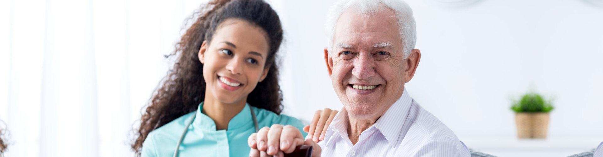 senior man and his nurse smiling