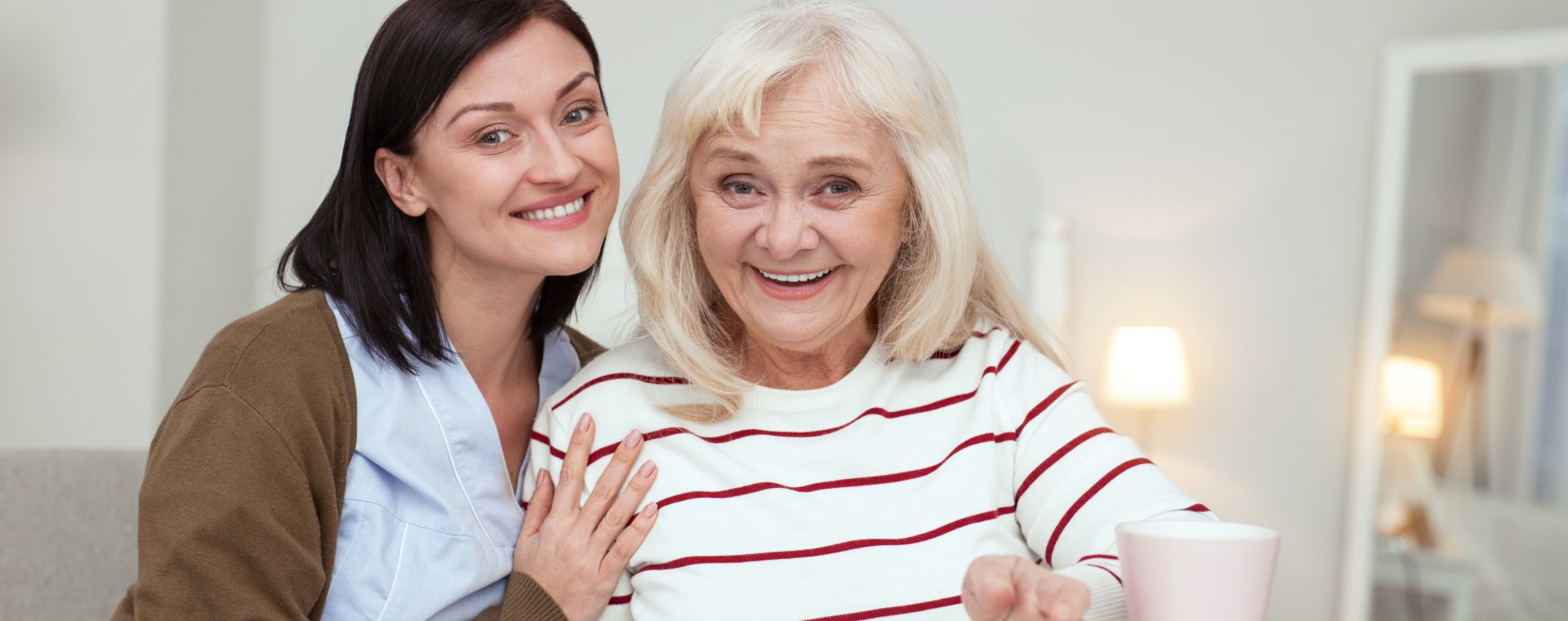 caregiver and her senior patient smiling
