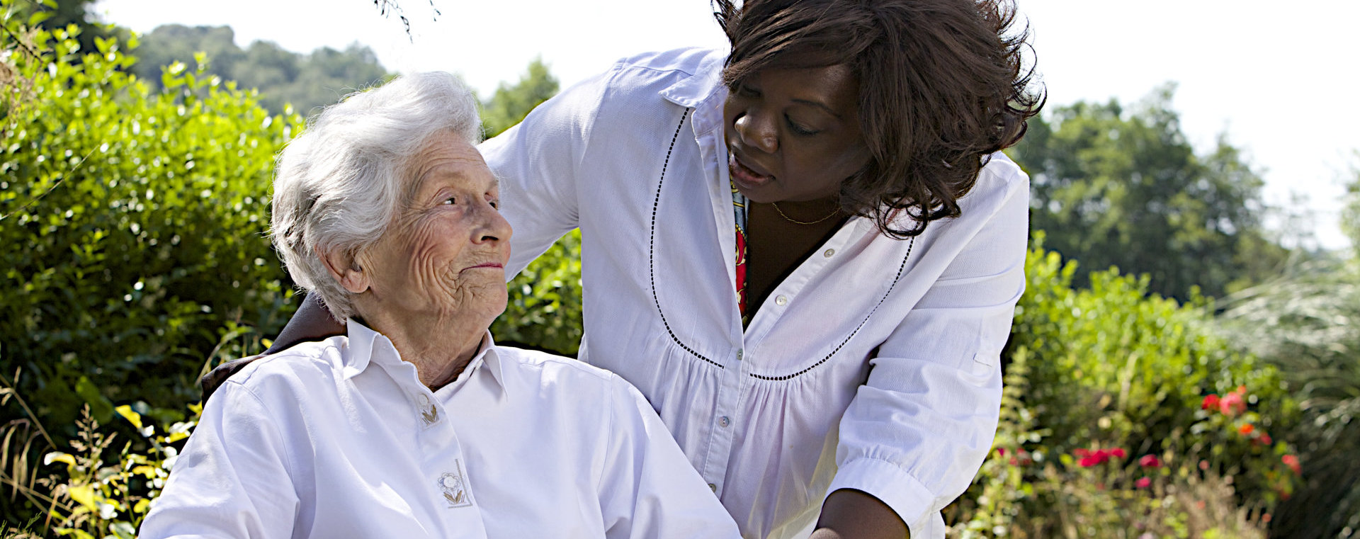 happy african caregiver and a senior woman