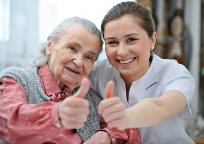 senior woman and her nurse giving thumbs up